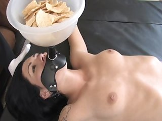 Beautiful bondage girl used as a bowl of chips holder