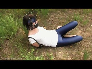 Girl in armbinder bound outdoors