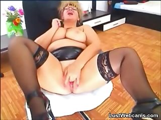 Busty mature in leather skirt fingering her pussy on webcam
