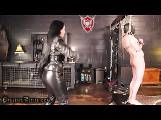 Domina in leather whips her slave