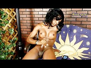 Shapely ebony pulls her huge erection spurting her load