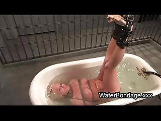Tied legs busty blonde lowered in water