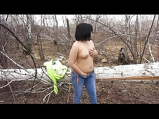 Brunette masturbates a shaved pussy in the forest, undressing outdoors.