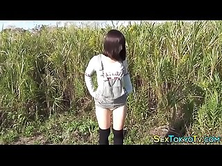 Asian teen rubs outdoors
