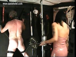 Beautiful horny mistress with big tits wearing latex dress hits dirty slave on his ass with a whip