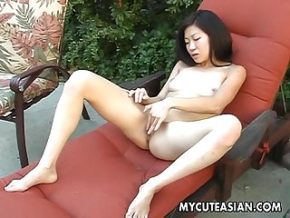 Naked brunette Asian chick rubbing her wet pussy solo